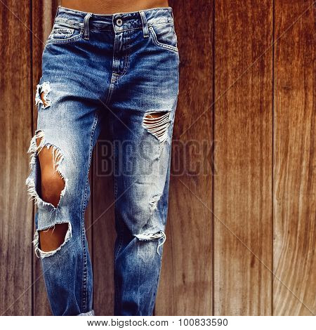Girl In Stylish Torn Jeans On Wooden Background