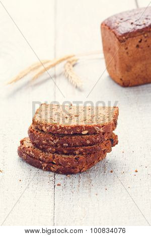 Loaf And Slices Of Bread With Spikelet Of Wheat On A Boards