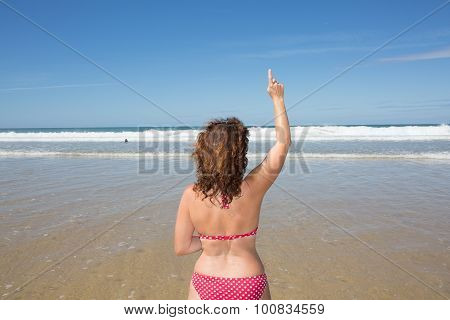 An Image Of A Girl Pointing Her Finger  In Front Of The Ocean - Copyspace