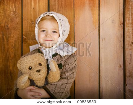 Portrait Of The Little Smiling Girl Wearing Vintage Clothes With Toy Bear