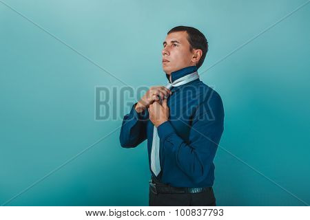 a man of European appearance thirty years straightens his tie on