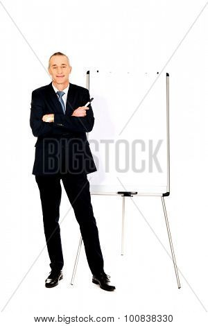 Mature businessman with marker standing near flip chart.
