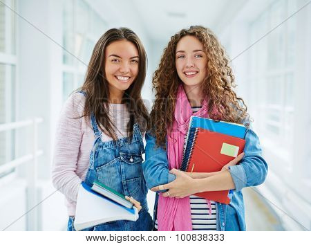 Happy teenage learners with books looking at camera