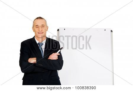 Mature businessman with marker near flip chart.