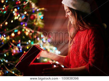 Female Santa opening magic box with gift on sparkling background