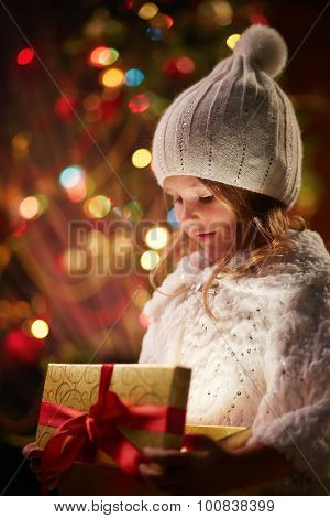 Adorable girl in white winterwear holding open magic giftbox