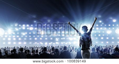 Back view of girl with hands up standing in stage lights