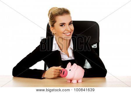 Businesswoman with a piggybank behind the desk.