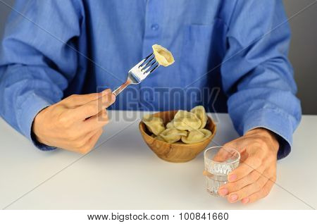 Young Man Eats Dumplings With Meat With Vodka