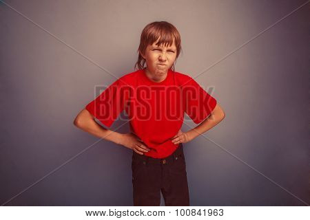 Boy, teenager, twelve years in the red shirt,  hands in the side