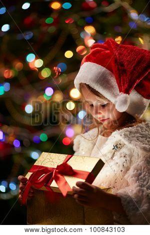 Cute child in Santa cap opening giftbox on xmas night