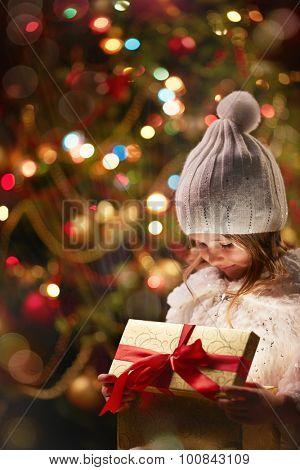 Adorable girl opening magic giftbox
