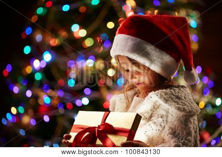 Cute child in Santa cap opening Christmas gift on sparkling background