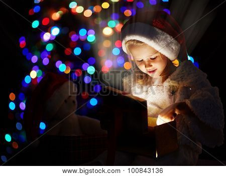 Cute girl holding open giftbox full of bright light