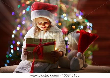 Surprised little girl looking at xmas present in golden giftbox