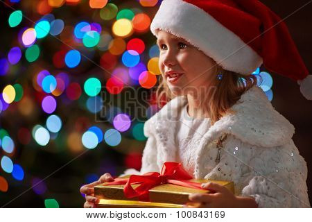 Cute girl in Santa cap holding giftbox on sparkling background