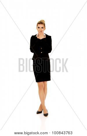 Young businesswoman covering with hand her mouth. Speak no evil concept.