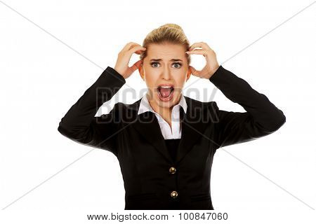 Angry businesswoman pulling her hair and screaming.
