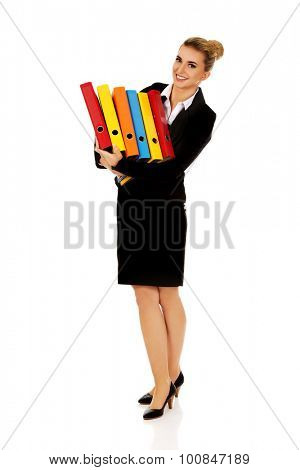 Young businesswoman carries heavy binders.