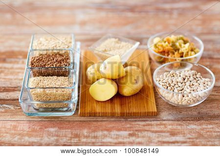 diet, cooking, culinary and carbohydrate food concept - close up of grain, pasta and beans in glass bowls with potatoes on table