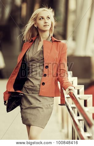 Young fashion business woman in red jacket with handbag walking on city street