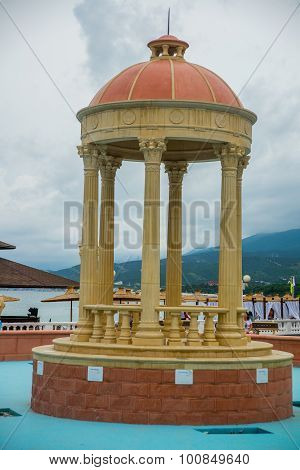 Rotunda. A small gazebo with beige columns near the water on a background of mountains.Summer.Russia