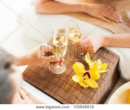 spa, health, resort, holidays and beauty concept - closeup og woman and man hands with champagne glasses