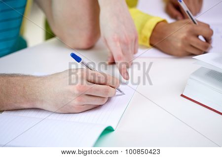 education, people and school concept - close up of students hands with notebooks writing at school