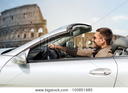 travel, tourism, road trip, transport and people concept - happy man driving cabriolet car over coliseum in rome background