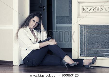 Beautiful fashion woman sitting in doorway at apartment
