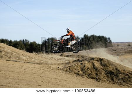 motorcycle jump from springboard in meadow outside