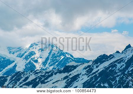 Snow on the mountains against the blue sky in the clouds.The Elbrus region.The Caucasus.