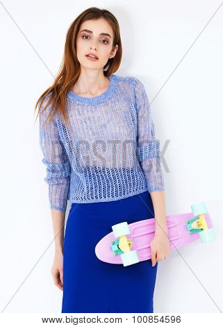 Vogue fashion model woman posing in blue skirt on white studio background.