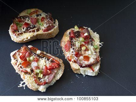 Three gourmet bruschetta made of bacon, tomatoes and cheese