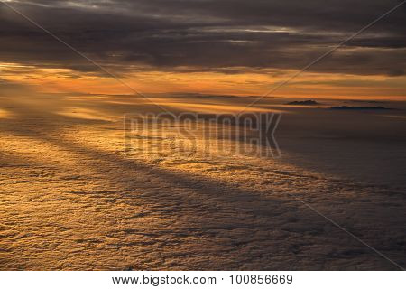 Sunset Over Clouds With Mountain Tops From Plane