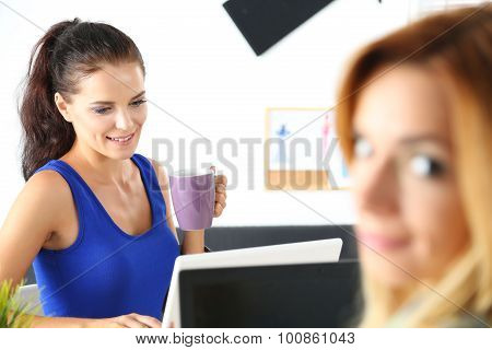 Two Female Designers In Office Drinking Morning Tea
