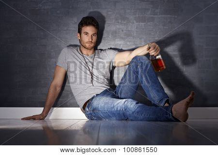 Handsome young man sitting on floor, drinking alcohol alone.