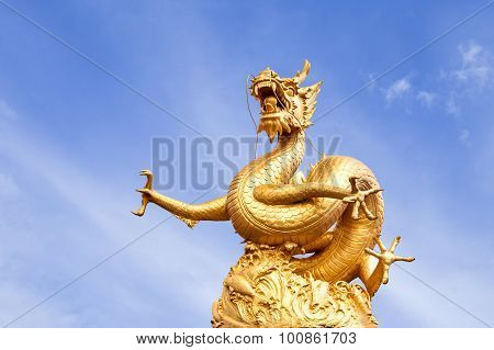 Chinese golden dragon statue on blue sky background.