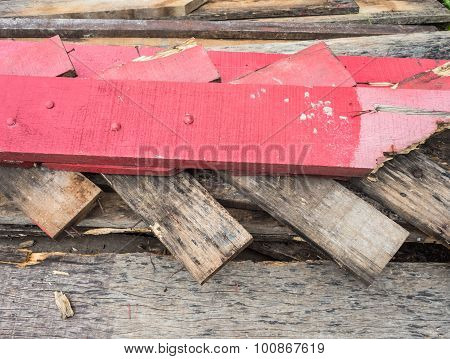 A scrap wood pile with protruding rusty nails.