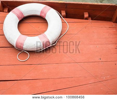 Lifebuoy tied with a rope - orange background for cruising.