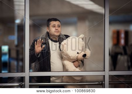 Man Holding Toy Bear And Looking Sadly Into The Distance.