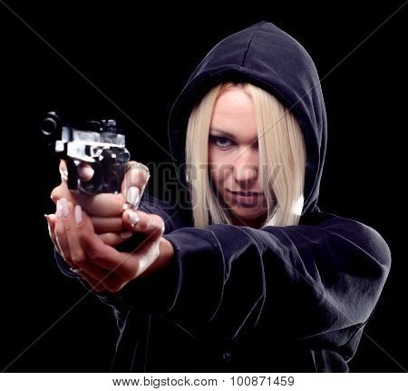 Female Criminal With Hood On Her Head Shooting With Gun On The Street At Night