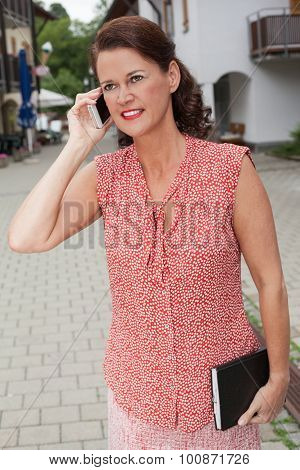 Businesswoman With Notebook Talking On Cell Phone