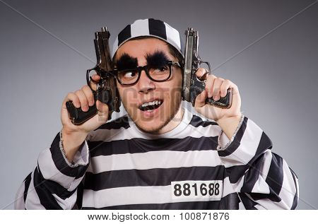 Young prisoner with handgun against gray