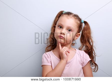 Fun Confused Kid Girl Thinking And Looking Serious About On Blue Background