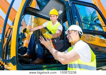 Asian construction machinery driver discussing with foreman blueprints on pad or tablet computer of building site