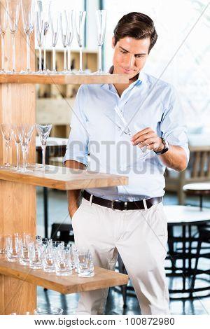 Man in furniture store choosing glasses standing in wooden shelf