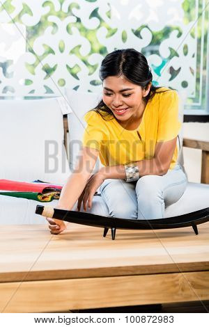 Asian Indonesian woman sitting on sofa couch in furniture store showroom with color and material catalog