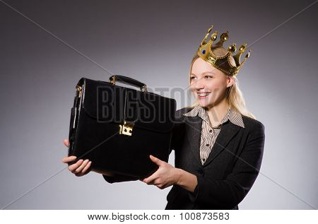 Businesslady wearing crown against gray
