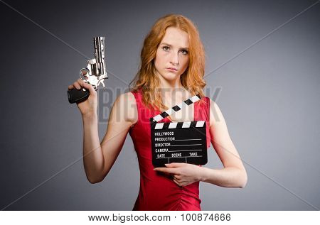 Girl in red dress with handgun and clapperboard against gray